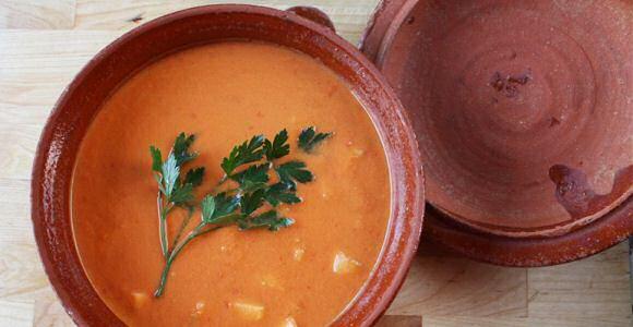 Lekkere koude gazpacho soep geserveerd in een aarden kom, gegarneerd met een twijgje platte peterselie