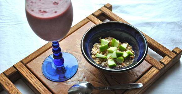 Gezonde tussendoortjes: een glas met fruit smoothie en een kom met ontbijtgranen en stukjes appel