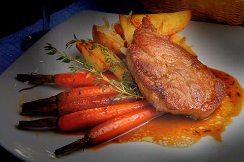 Gebakken aardappelen met wortelen en varkenskotelet